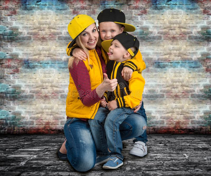 A young mother and two young sons in the style of hip hop.Fashionable family.Graffiti on the walls. royalty free stock photos