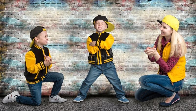 A young mother and two young sons in the style of hip hop.Fashionable family.Graffiti on the walls. royalty free stock image