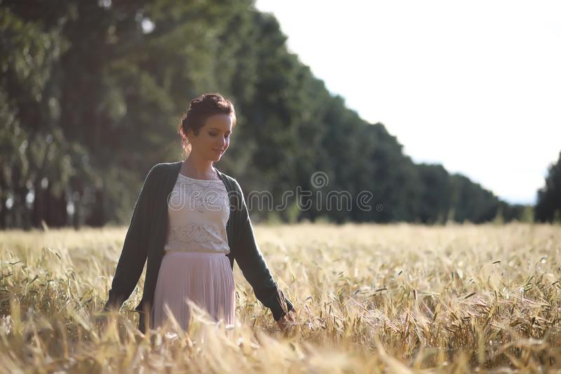A young mother walk in wheat fields royalty free stock images