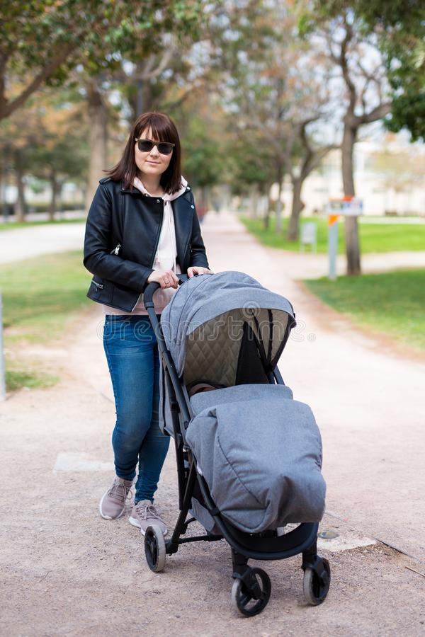 Young mother walking with baby carriage in spring park. Portrait of young mother walking with baby carriage in spring park stock images