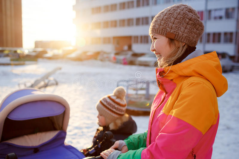 Young mother walking with baby child stroller in winter at sunset. royalty free stock photography