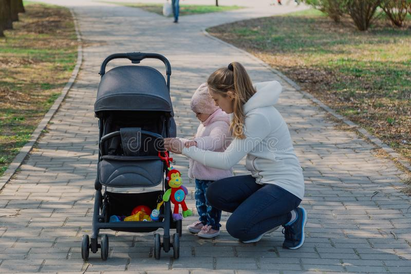 A young mother walks with a child who rolls a pram. royalty free stock images