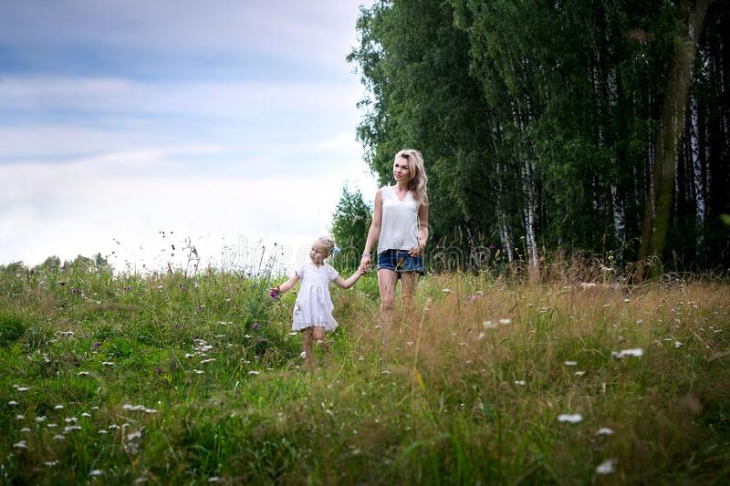 A young mother walks through a meadow with a little girl. Summer day, wildflowers, birch stock images