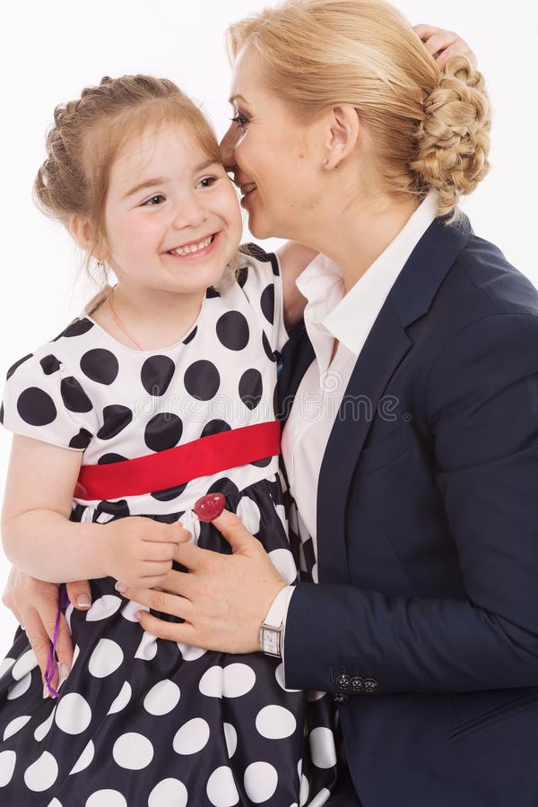 Young mother whispers to daughter in ear, close-up stock photography