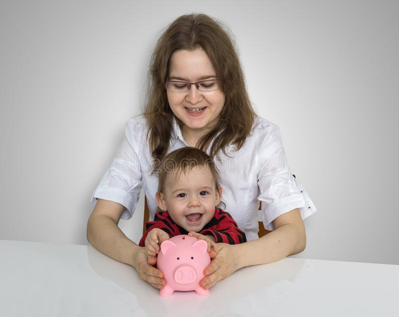 Young mother wit her child is collecting coins in piggy money ba stock photo