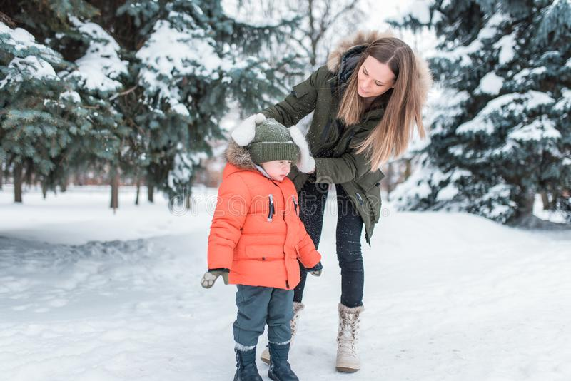 A young mother, a woman shakes off a boy`s snow 4-6 years old son. In winter in the park outside. Caring for baby stock photo