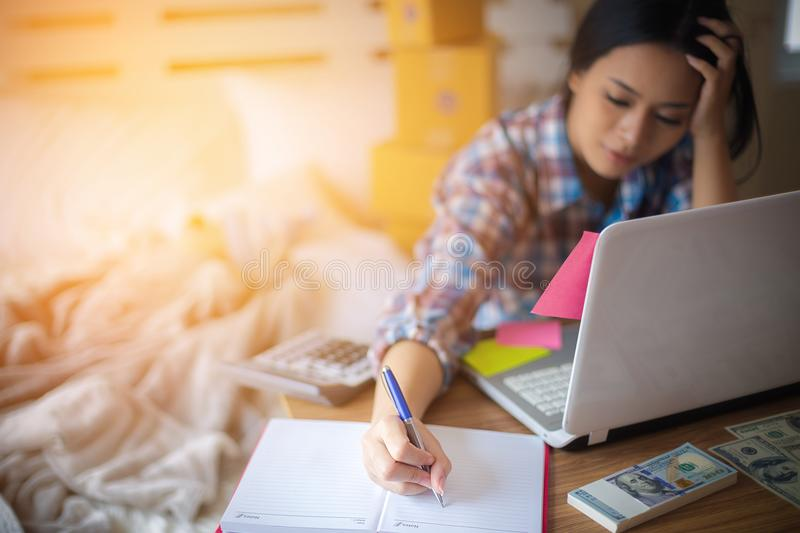 Young mother and work at home. Young mother writing in red book for checking order from laptop on wooden table, baby lying on bed and packaging stacked behind royalty free stock image