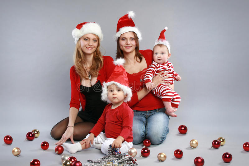 Young mothers with children in Christmas hats. On a grey background stock photos