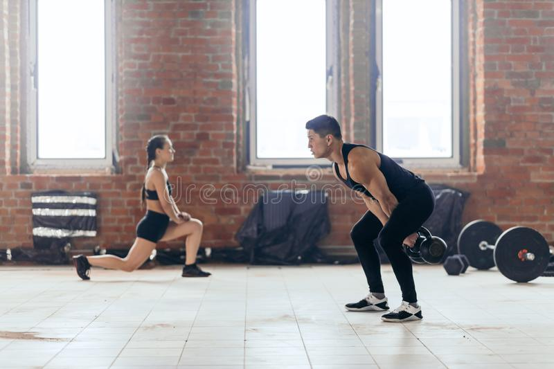 Young motivated couple working out at gym royalty free stock images