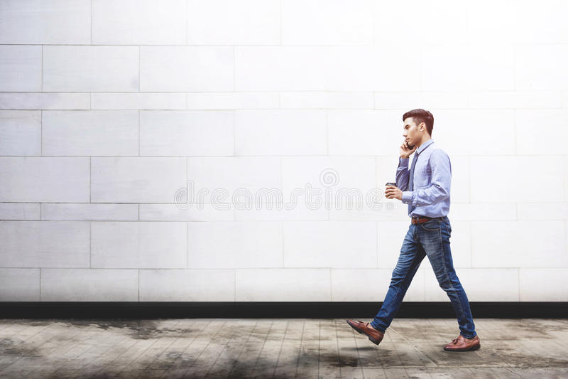 Young motivation Businessman talk via smart phone while walk out. Door building, Lifestyle of modern male use technology to communicate in business concept royalty free stock images