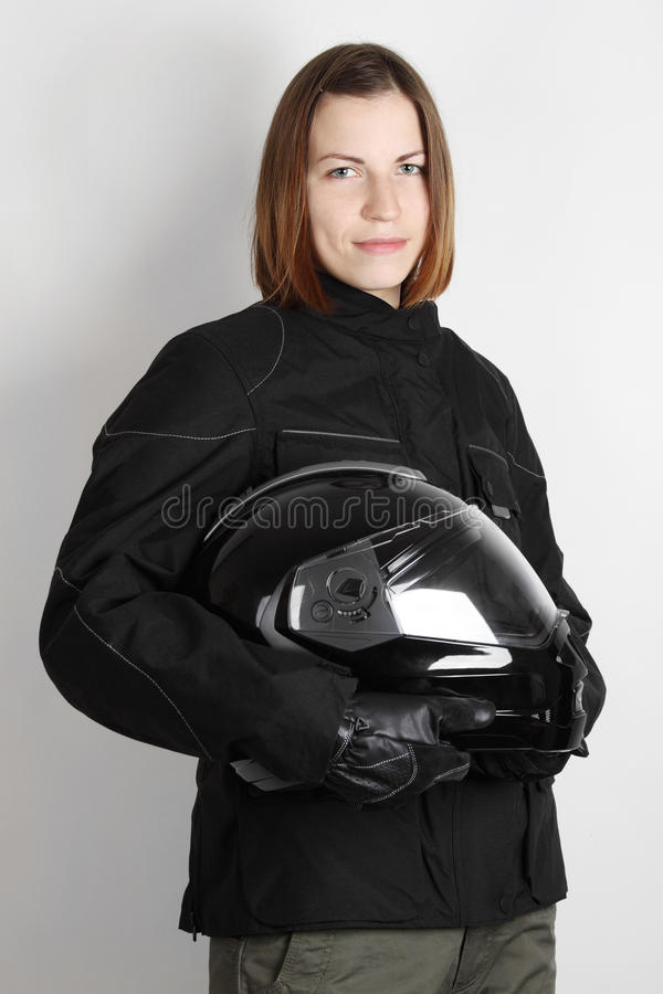 Young motorcyclist woman holding helmet in studio royalty free stock image
