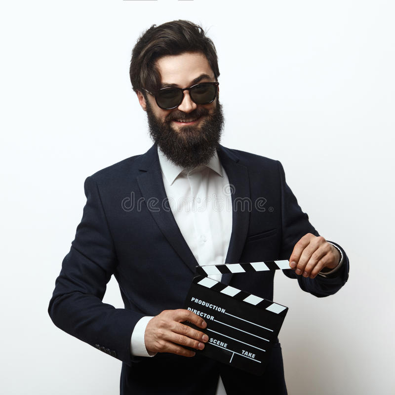 Young movie director holding a clapperboard. And looking at the camera isolated on white background. Smiling bearded man in sunglasses stock photos