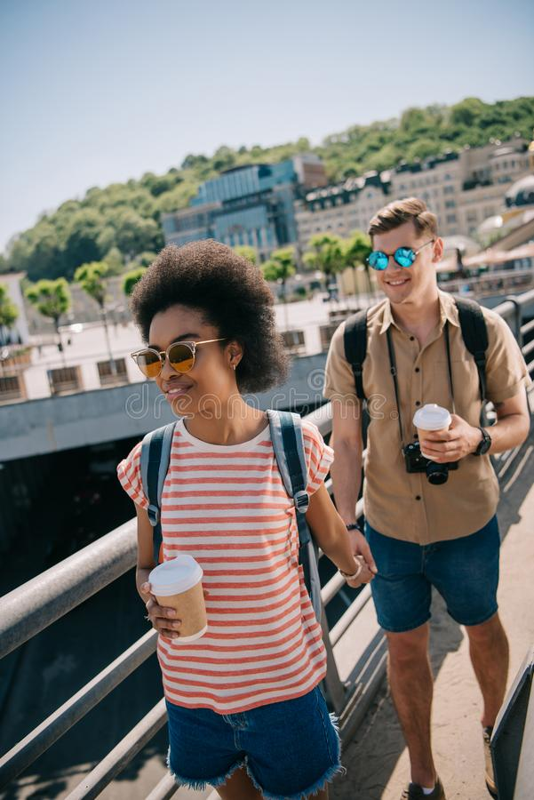 young multicultural couple of tourists with coffee cups and camera walking royalty free stock images