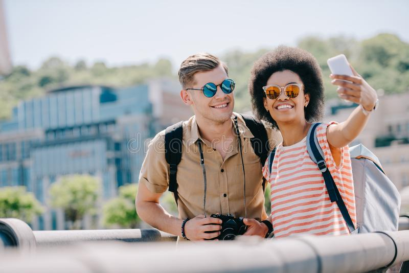 young multicultural couple of travelers taking selfie royalty free stock photos