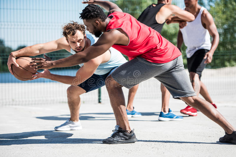 Young multicultural men playing basketball on court royalty free stock photos