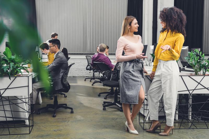 Young multiethnic businesswomen talking and smiling each other while colleagues working behind royalty free stock photo