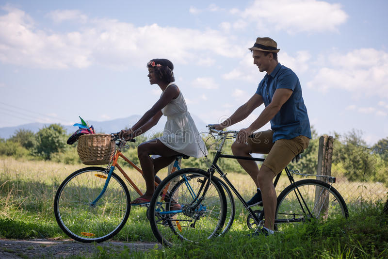 Young multiethnic couple having a bike ride in nature royalty free stock photos