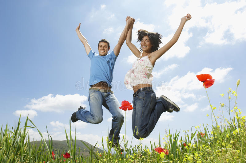 Young Multiethnic Couple Jumping In Poppy Field stock photography