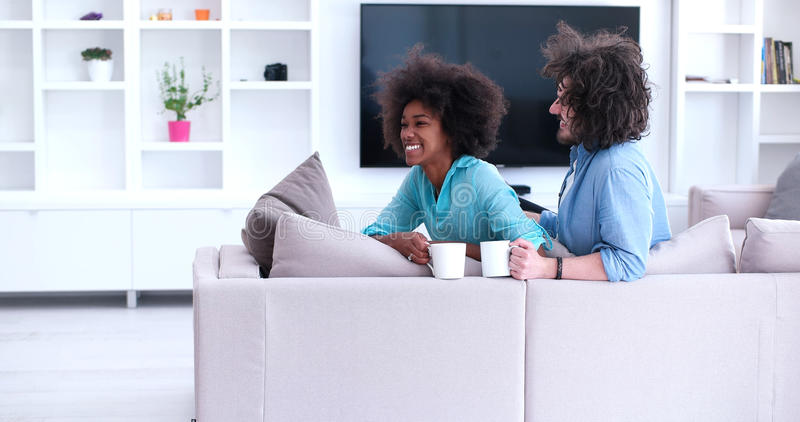 Multiethnic couple sitting on sofa at home drinking coffe stock photography