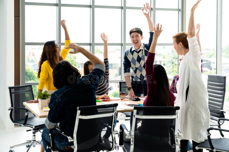 Young multiethnic diverse creative asian group huddle and high five hands together in office workshop with success or empower royalty free stock photos