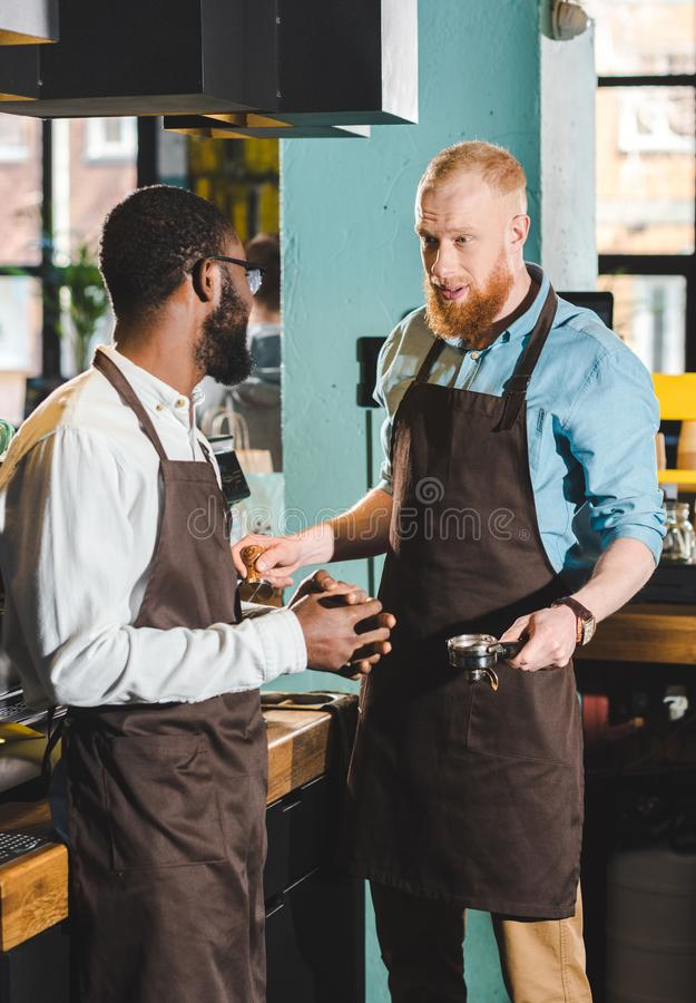 young multiethnic male owners of coffee shop in aprons talking stock photography