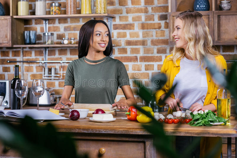 Young multiethnic women cooking together and smiling each other stock photos