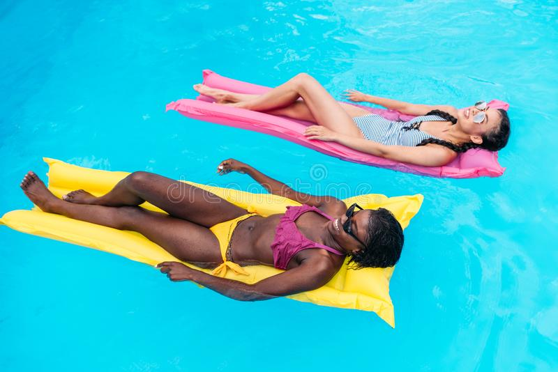 Young multiethnic women floating on inflatable mattresses in swimming pool royalty free stock images