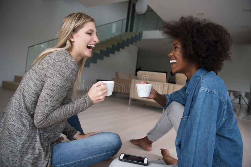 Young multiethnic women sit on the floor and drinking coffee stock image