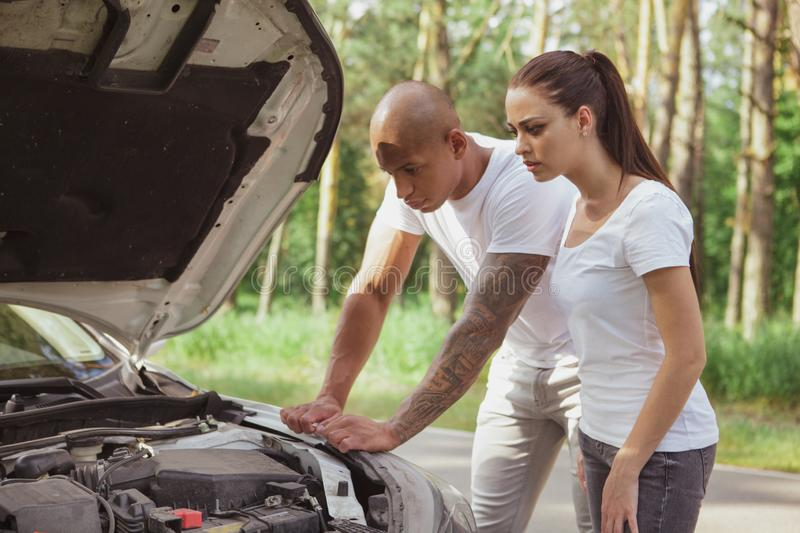 Young multiracial couple with a broken car in the middle of the road royalty free stock image