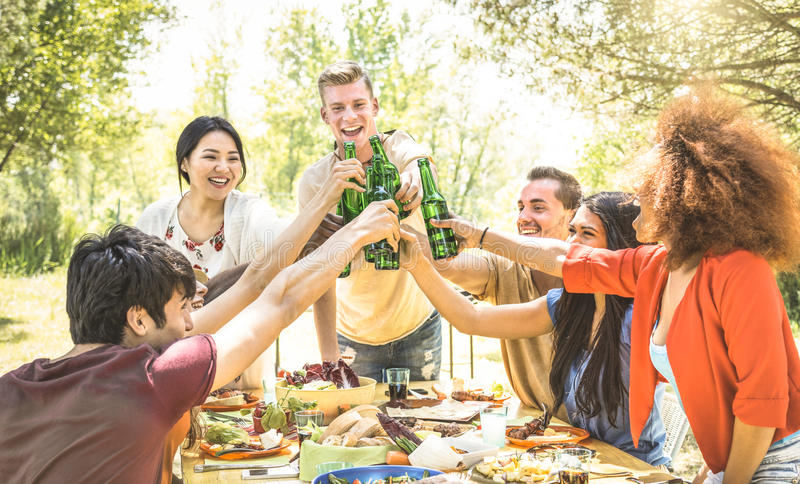 Young multiracial friends toasting at barbecue garden party. Friendship concept with happy people having fun at backyard bbq summer camp stock images