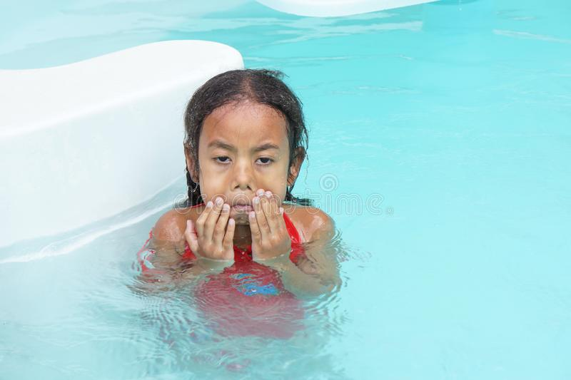 Young multiracial girl child learning to swim stock photo