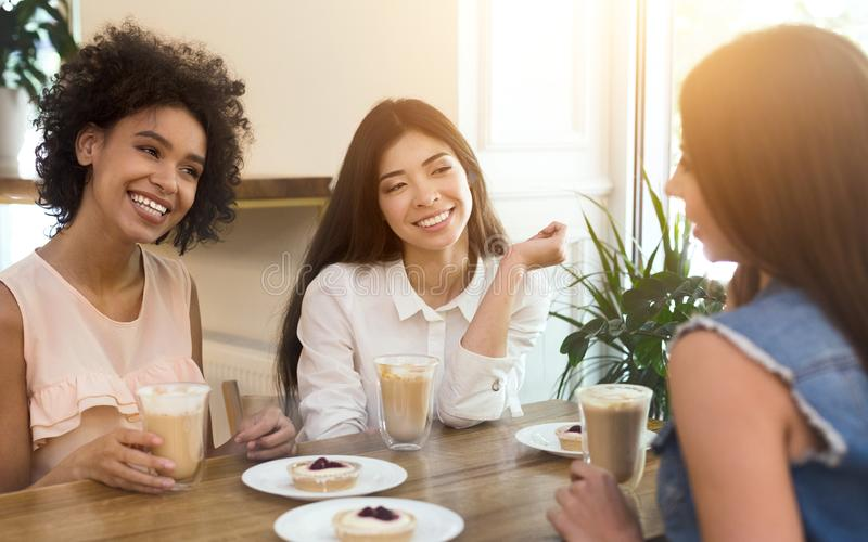 Young multiracial girls sitting in cafe, drinking coffee and smiling stock image