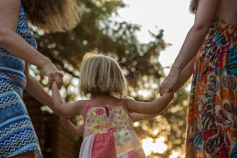 Young mum with blonde daughter girls smiling doing ring around the rosie . Warm sunset light. Family summer travel. Vacations at sea or ocean stock images