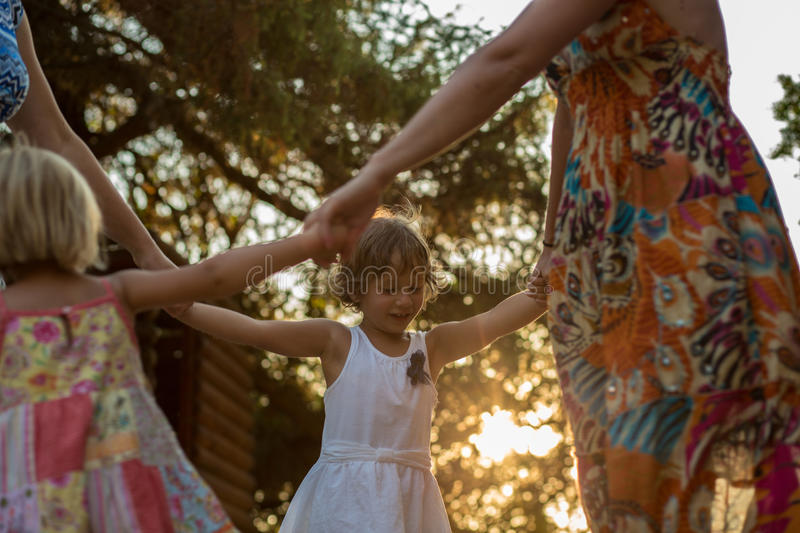 Young mum with blonde daughter girls smiling doing ring around the rosie . Warm sunset light. Family summer travel. Vacations at sea or ocean stock photography