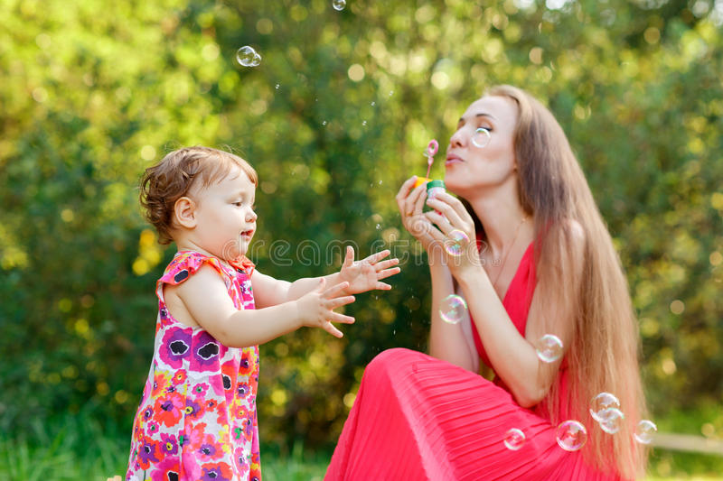 Young mum with daughter blowing soap bubbles stock images