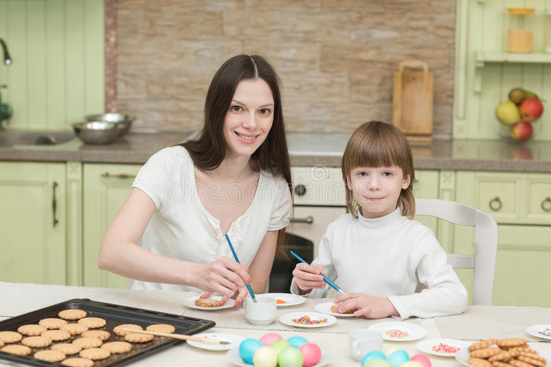 Young mum and her little son baking together and decorating the cupcakes stock image
