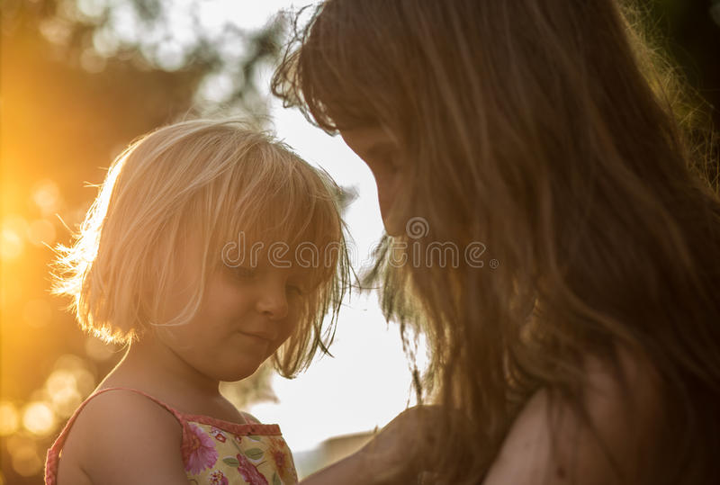 Young mum holding his blonde daughter girl on his arms. Warm sunset light. Family summer travel vacations at sea or stock photo