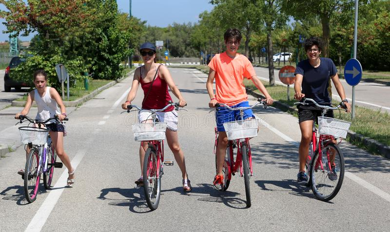 Young mum with three children on bicycles. Pedal through the city streets in the summer royalty free stock photo