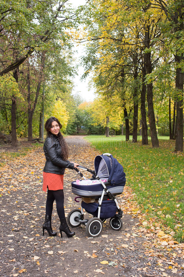 Young mum walks with pram in the autumn yellow park stock images