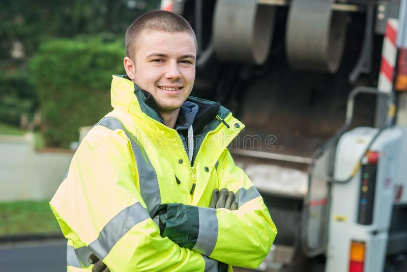 Young municipal garbage collector near garbage truck stock images