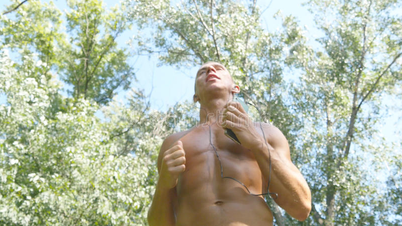 Young muscular athlete running at the forest path. Active strong man training outdoors. Fit handsome athletic male stock photos