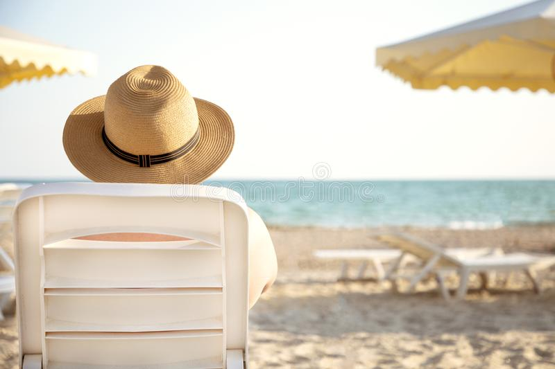 Young muscular attractive man in a hat lies on the lounger and looking at the sea or ocean. View from the back stock photography