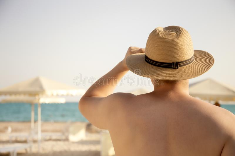 Young muscular attractive man in a hat looking at the sea. View from the back. Turquoise water and white sand. Vacation stock photos