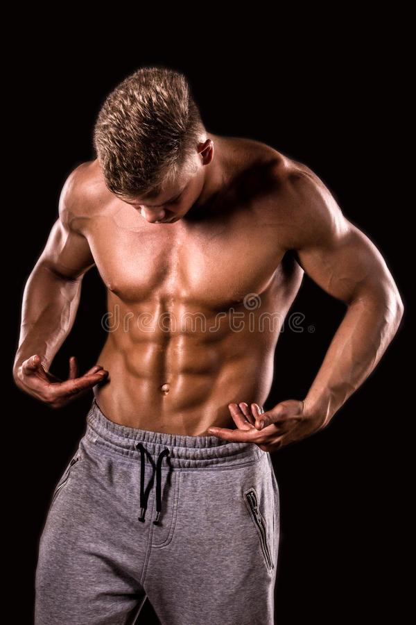 Young muscular bodybuilder boy showing his abdominal muscle royalty free stock photography