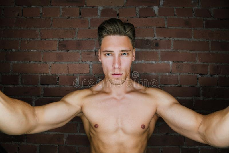 Young muscular bodybuilder fitness model posing against a brick wall loft fitness club. Beauty Ring flash. stock photography