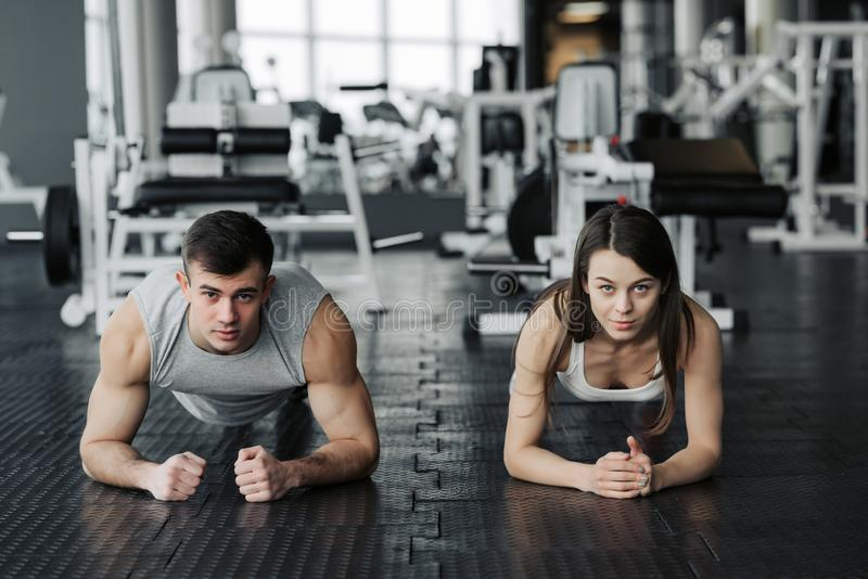 Young muscular couple doing doing hard workout at the gym. Doing plank in the gym royalty free stock image