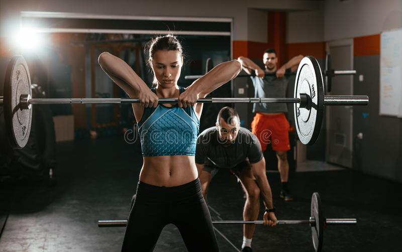 Gym Day. Young muscular cute women doing exercise with barbell at the gym. Behind her there are here friends exercising stock images