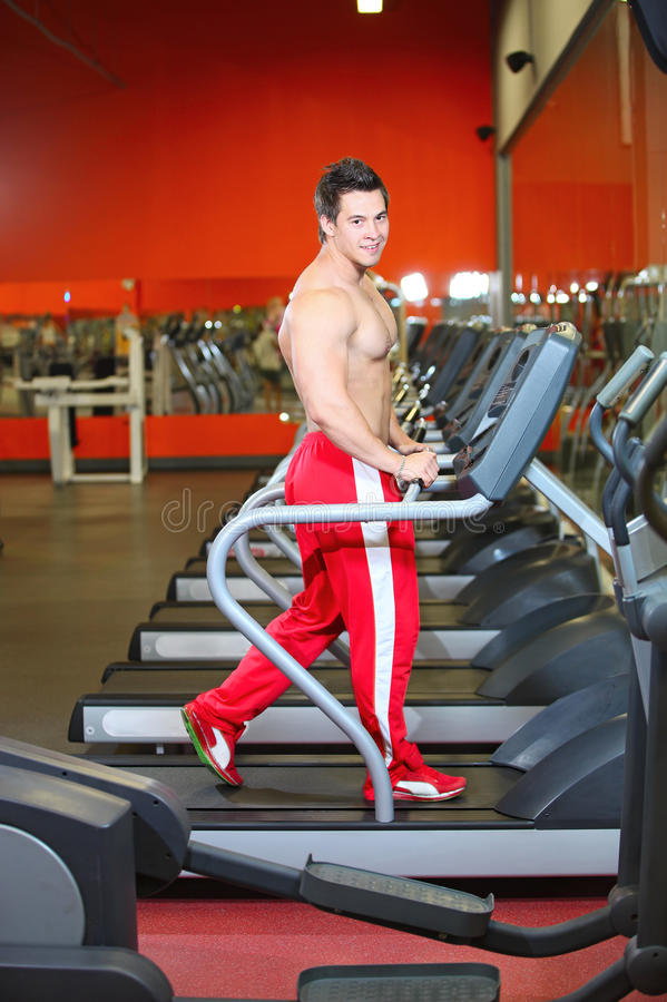 Young muscular guy working out on a treadmill royalty free stock photography