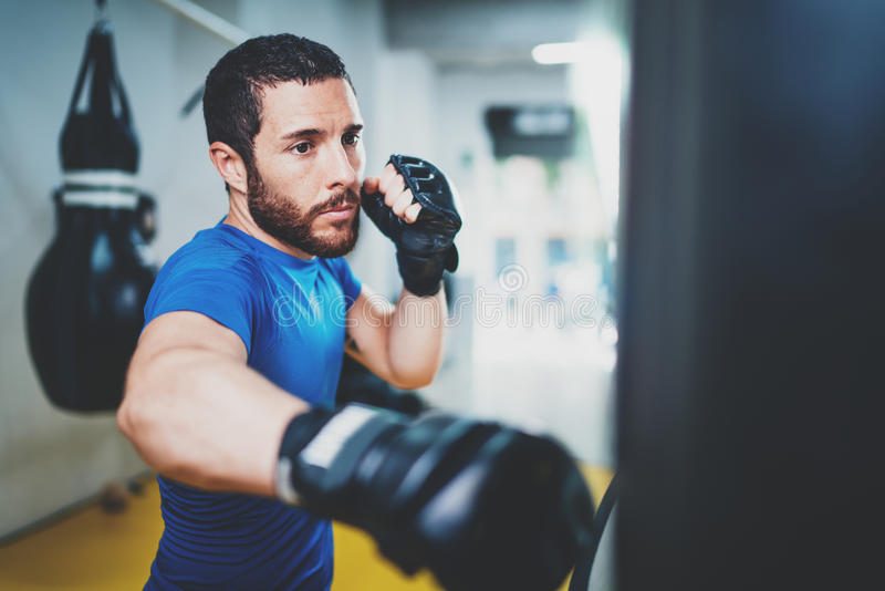 Young muscular kickboxing fighter practicing kicks with punching bag.Kick boxer boxing as exercise for the fight.Boxer royalty free stock photos