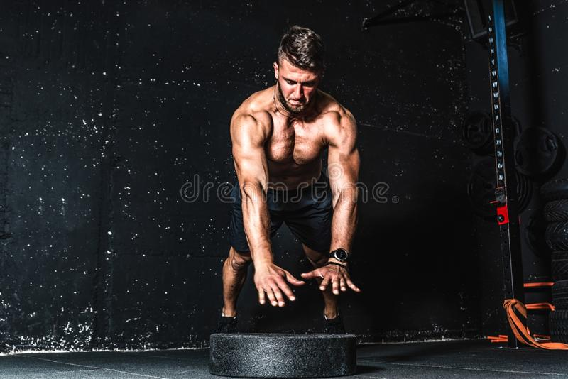Young muscular man with big sweaty muscles doing push ups workout training with jump his hand above the barbell weight plate on th. Jump push ups, Young muscular stock images